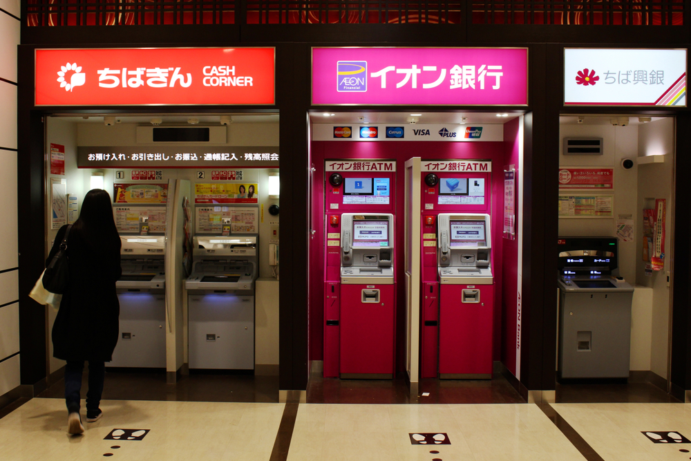 A customer approaches a row of ATMs (including Chiba Ginko and Aeon Ginko) in an Aeon Mall in Makuhari.